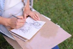 Main des courses de crayon de Makes Sure Sharp d'artiste de fille sur l'album PAG Images libres de droits