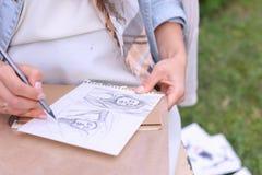 Main des courses de crayon de Makes Sure Sharp d'artiste de fille sur l'album PAG Images stock