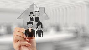 Main dessinant la maison 3d avec l'icône de famille Photo libre de droits