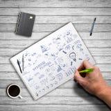 Main dessinant un griffonnage d'affaires Photographie stock libre de droits
