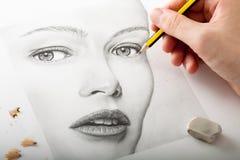 Main dessinant un visage de femme Photographie stock libre de droits