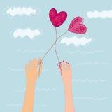 Main deux avec des ballons de coeurs Image libre de droits