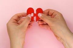 Main deux tenant le puzzle denteux en deux pièces se reliant de coeur d'amour, concept d'amour Photo stock