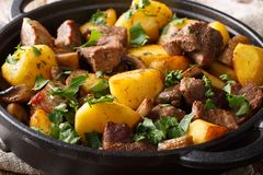 The main dish of fried pork with potatoes and mushrooms close-up in the pan. horizontal royalty free stock photo