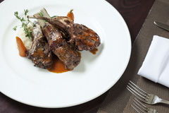 Main dish. Plate with roast ribs  of lamb with potato  on color back Stock Images