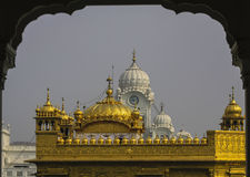 Main Dome of Golden Temple seen through Arch. The white Domed Clock Tower and the clear grey sky provide a contrasting background to the Main Dome of the Golden Stock Photo