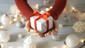 Main donnant à cadeau la décoration de Noël blanc banque de vidéos