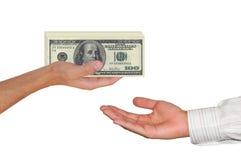 Main donnant 100 dollars à une autre main Images libres de droits