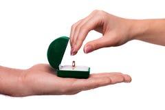 Main donnant la boîte avec un anneau de mariage Photographie stock libre de droits