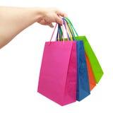 Main donnant les sacs à provisions de papier colorés Photos libres de droits