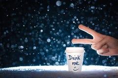 Main drôle avec la tasse de papier avec le thé sur le fond de neige ; Photo libre de droits
