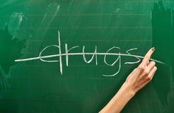 Main droite d'une protestation de drogue d'écriture d'adolescente sur le conseil pédagogique vert images stock