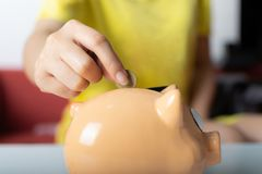 Main droite haute étroite de femme mettant une pièce de monnaie dans la tirelire photographie stock libre de droits