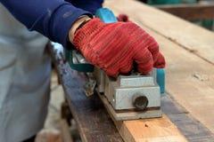 Main du charpentier à l'aide de la planeuse électrique avec la planche en bois dans l'atelier de menuiserie Images stock