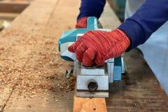 Main du charpentier à l'aide de la planeuse électrique avec la planche en bois dans l'atelier de menuiserie Photographie stock libre de droits