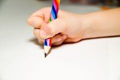 Main du rigth de l'enfant tenant un crayon dessus au-dessus de blanc Photo stock