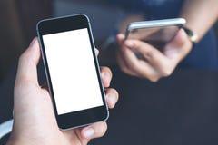 Main du ` s d'homme d'affaires tenant le téléphone portable noir avec l'écran blanc vide avec le fond de femme d'affaires Photo libre de droits