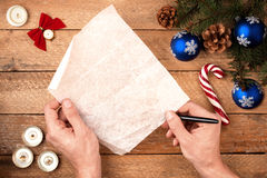 Main du ` s d'homme de fond de Noël avec un stylo, tenant une lettre sur Photographie stock