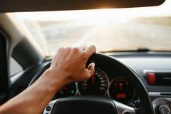 Main du ` s d'homme de foyer sélectif sur le volant, conduisant une voiture au coucher du soleil fond plus de ma course de portef images libres de droits