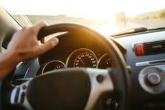 Main du ` s d'homme de foyer sélectif sur le volant, conduisant une voiture au coucher du soleil fond plus de ma course de portef photographie stock libre de droits
