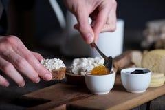 Main du ` s d'homme mettant la confiture sur le pain avec du fromage de ricotta Images stock