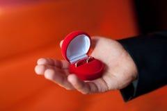 Main du ` s d'homme tenant la bague de fiançailles Photographie stock