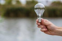 Main du ` s d'hommes jugeant l'ampoule électrique Photos libres de droits