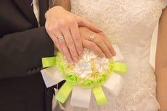 Main du ` s de femelle et d'homme des nouveaux mariés avec des anneaux sur un bouquet avec Photo libre de droits