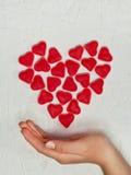 Main du ` s de femme avec le coeur fait à partir des bonbons à gelée Images stock