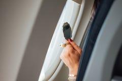 Main du ` s de femme avec un grand anneau et un miroir de coiffeuse dans un avion Photographie stock libre de droits