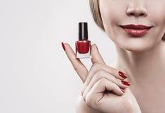 Main du ` s de femme avec une bouteille de vernis à ongles rouge D'isolement sur le fond blanc Image libre de droits