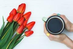 Main du ` s de femme tenant la tasse avec du café et les tulipes rouges Photo stock