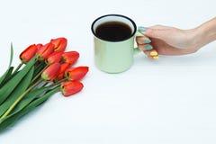 Main du ` s de femme tenant la tasse avec du café et les tulipes rouges Photos stock