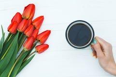 Main du ` s de femme tenant la tasse avec du café et les tulipes rouges Images libres de droits