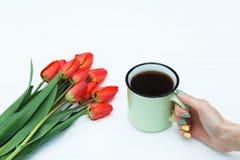 Main du ` s de femme tenant la tasse avec du café et les tulipes rouges Photographie stock