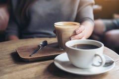 Main du ` s de femme tenant la tasse de café de latte sur la table en bois de vintage en café Photo stock