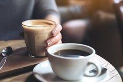 Main du ` s de femme tenant la tasse de café de latte sur la table en bois de vintage en café Photo libre de droits