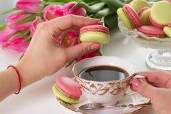 Main du ` s de femme tenant le macaron ou le dessert rose de macaron Images libres de droits