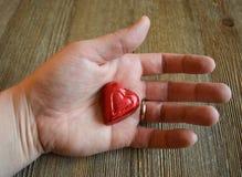 Main du ` s de femme tenant un coeur de sucrerie Photo stock