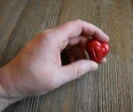 Main du ` s de femme tenant un coeur de sucrerie Photographie stock
