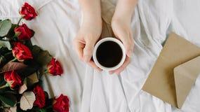 Main du ` s de femme, une tasse de café noir et un bouquet des roses rouges, enveloppe avec des félicitations Photos stock
