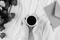 Main du ` s de femme, une tasse de café noir et un bouquet des roses rouges, enveloppe avec des félicitations Image libre de droits