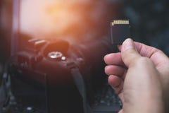 Main du ` s de photographe tenant la carte de mémoire Photos stock