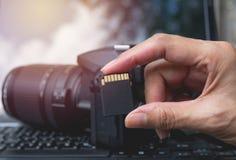 Main du ` s de photographe tenant la carte de mémoire Photographie stock libre de droits