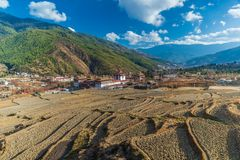Tashichho Dzong, with rice fields in the foreground during winter time stock images