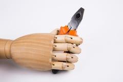Main en bois tenant des pinces Image stock