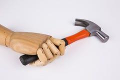 Main en bois tenant le marteau Photo stock