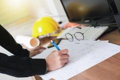 Main en gros plan des documents masculins d'écriture d'architecte sur l'espace de travail Photographie stock libre de droits