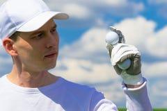 Main enfilée de gants tenant une boule de golf Photo stock