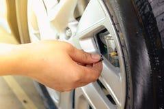 Main enlevant un noir de pneu Image stock